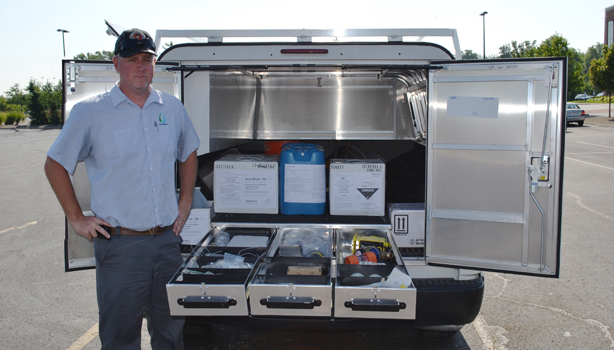 Chardon Labs worker behind a truck displaying supplies and tools for services